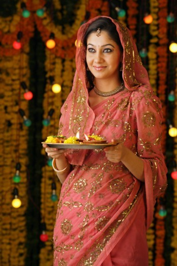 Portrait of a woman holding pooja thali with dias : Stock Photo