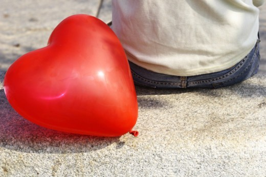 Stock Photo: 1491R-1181792 Rear view of a woman sitting behind a heart shaped balloon