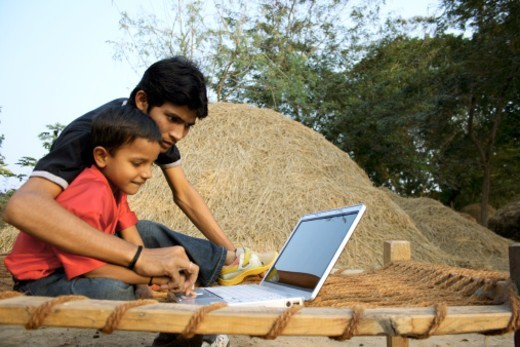 Stock Photo: 1491R-1182736 Father and son working on laptop