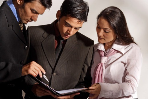 Businessmen and businesswoman cross checking the file : Stock Photo