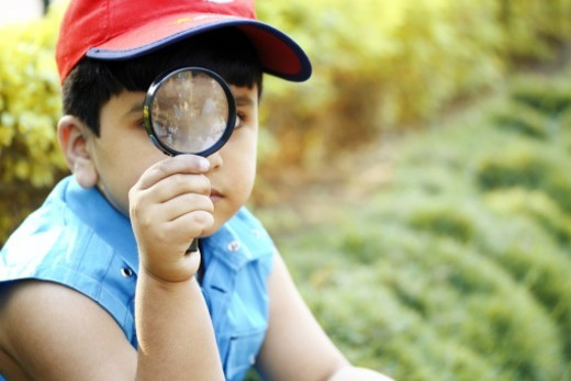Young boy looking through a magnifying glass : Stock Photo