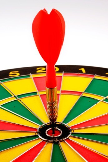 Close up of a dart in center of a dart board : Stock Photo