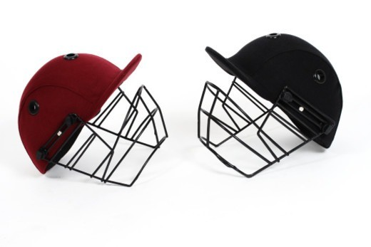 Two cricket helmets facing each other , studio shot : Stock Photo