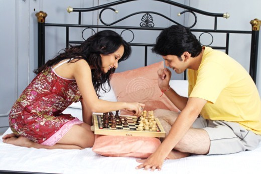 A young couple playing chess : Stock Photo