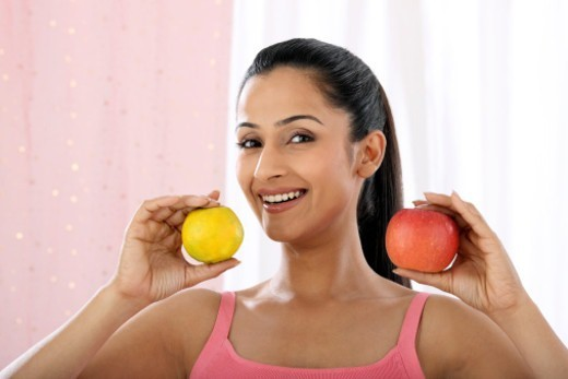 Stock Photo: 1491R-1185881 Young woman holding an orange and an apple