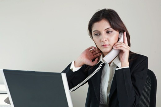 Businesswoman using laptop, talking on telephone : Stock Photo
