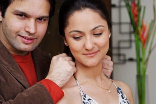 Man adorning a woman with jewelry : Stock Photo