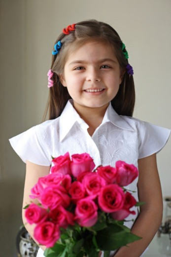 Girl holding a bouquet of red roses : Stock Photo