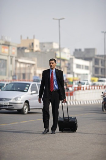 Stock Photo: 1491R-1188356 Businessman walking on the road pulling roller suitcase