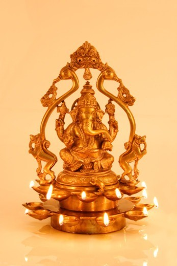 A lit golden staue of Lord Ganesh : Stock Photo