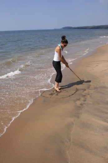 Stock Photo: 1491R-1188643 Young woman drawing in sand at beach
