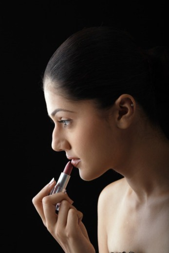 Side view of a young woman applying lipstick : Stock Photo