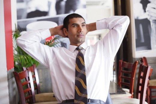 Stock Photo: 1491R-1190087 A young businessman relaxing on a chair