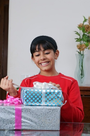 Stock Photo: 1491R-1190143 Girl opening a gift pack