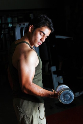 Stock Photo: 1491R-1190826 A young man holding dumbbell