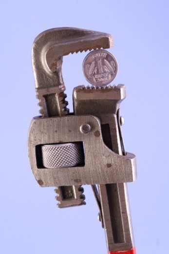 A coin held by a wrench : Stock Photo