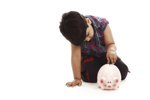 Portrait of a boy putting a coin into a piggy bank : Stock Photo