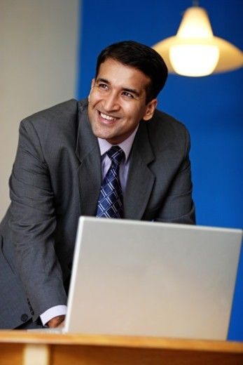 Stock Photo: 1491R-1191716 Portrait of a businessman working on a laptop