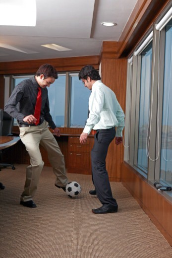 Stock Photo: 1491R-1191888 Young businessmen playing football in office