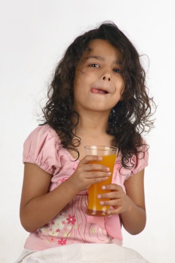 Stock Photo: 1491R-1191967 Young girl holding a glass of juice