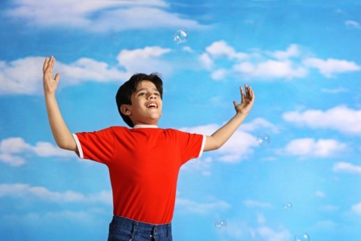Boy playing with soap bubbles : Stock Photo