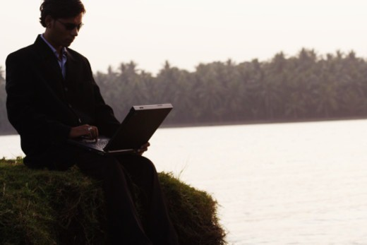 An executive using a laptop by a river : Stock Photo
