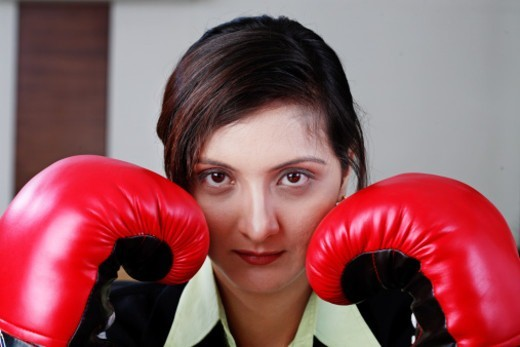 Businesswoman wearing boxing gloves, portrait : Stock Photo