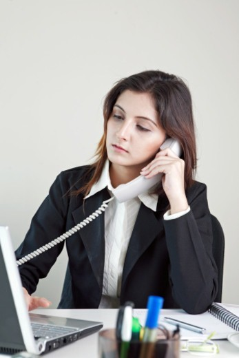 A young businesswoman working on a laptop, talking on telephone : Stock Photo