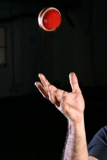 Person flinging a Cricket ball : Stock Photo