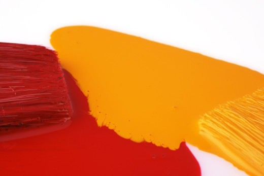 Two paint brushes painted in red and yellow paint : Stock Photo