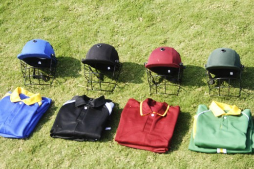 Cricket helmets and jerseys on the ground : Stock Photo