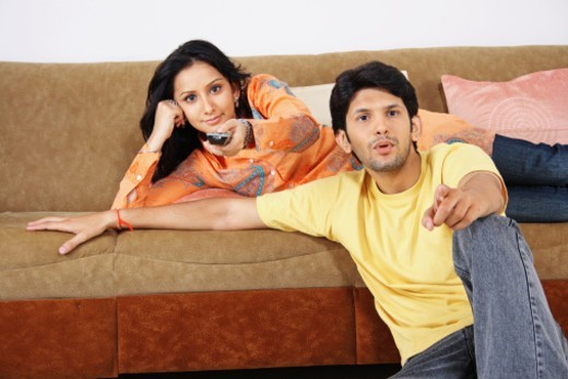 A young couple watching television : Stock Photo