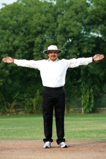 Stock Photo: 1491R-1194589 Cricket umpire signaling wide ball