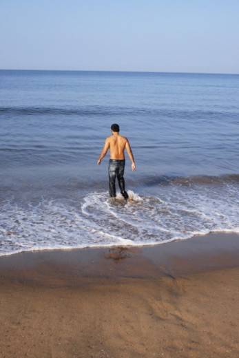 Rear view of a man walking into the sea : Stock Photo