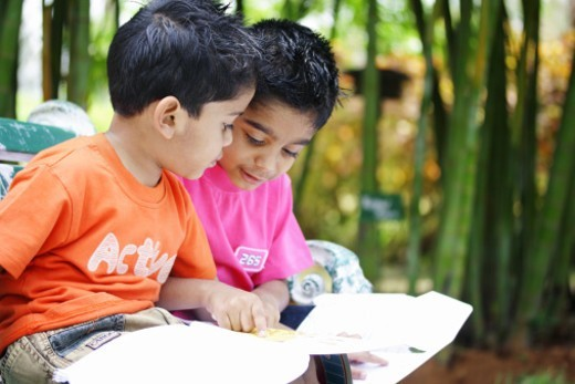 Two kids sitting with a colouring book in a park : Stock Photo