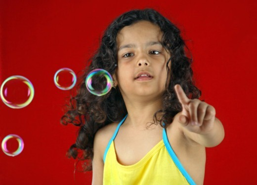 Stock Photo: 1491R-1195495 Girl playing with soap bubbles