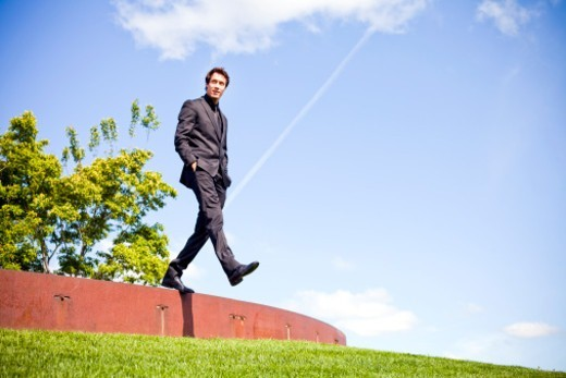 A well dressed young man stepping off a ledge outside in a grassy area. : Stock Photo