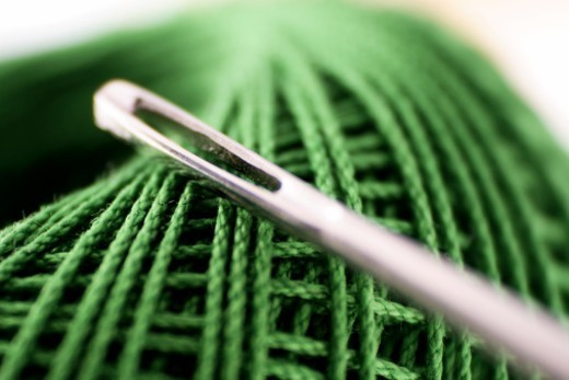 Close up of a thread spool and a needle : Stock Photo
