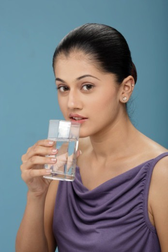 Stock Photo: 1491R-1196065 Young woman holding a glass of water