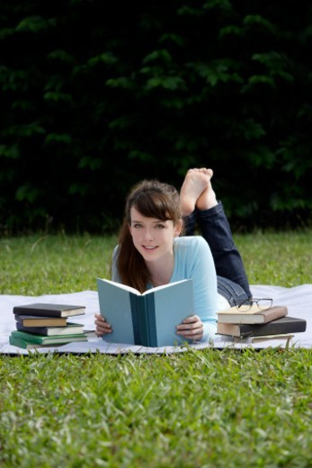 Stock Photo: 1491R-1196701 young woman reading outdoors