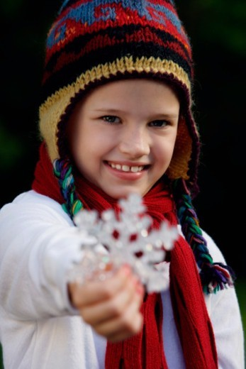 young girl wearing hat and holding snowflake : Stock Photo