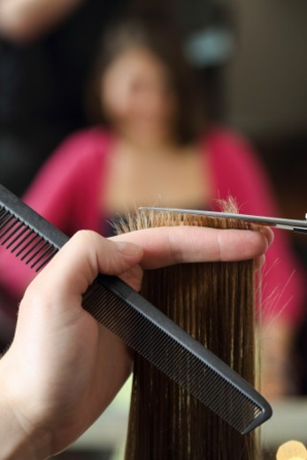 a wisp of hair gets cut by a hairdresser : Stock Photo