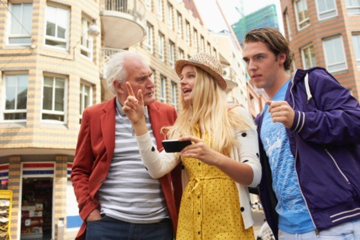 Stock Photo: 1491R-1198549 Teenage girl using cell phone for directions in city with brother and grandfather