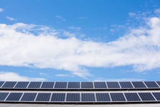 Environmentally friendly rooftop solar panels for generating green electricity and a blue sky with light cloud : Stock Photo