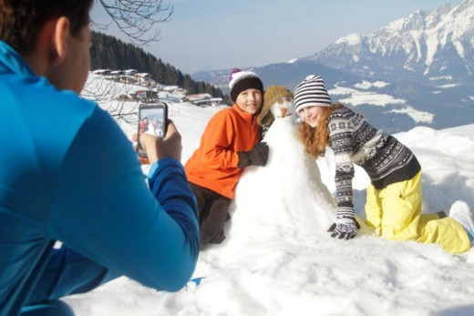 Teenage boy taking picture with cell phone of girls making snowman : Stock Photo