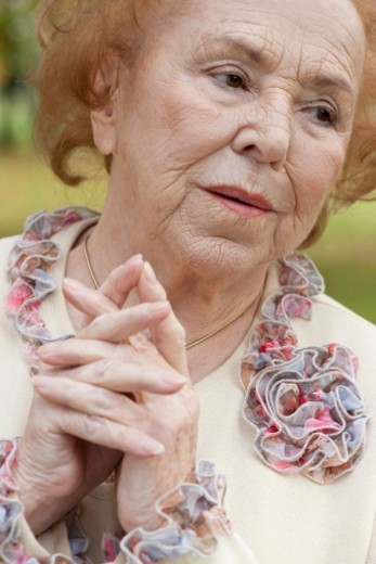 Stock Photo: 1491R-1199763 Senior woman with hands clasped in park