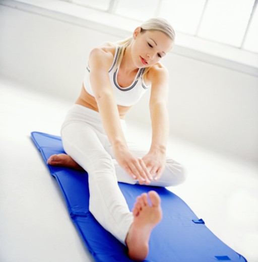 a young woman performing stretching exercises on a exercise mat : Stock Photo