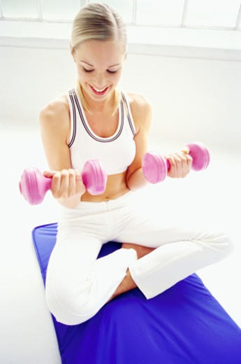a young woman exercising with dumbbells on a exercise mat : Stock Photo