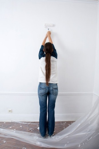Stock Photo: 1491R-1201396 Young Woman Painting Wall With Roller