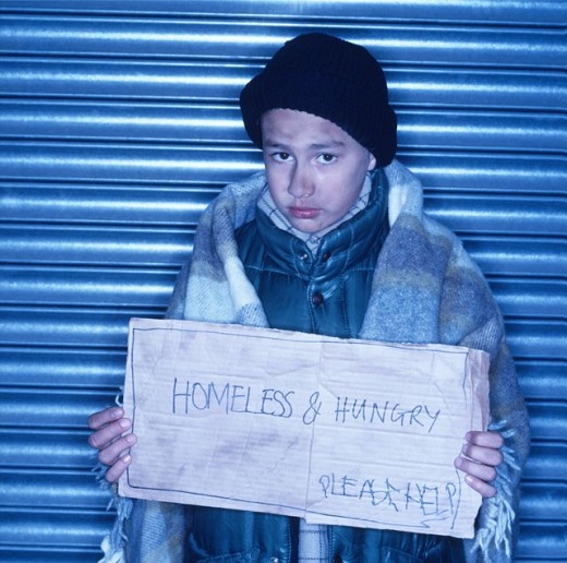homeless young boy holding a sign : Stock Photo